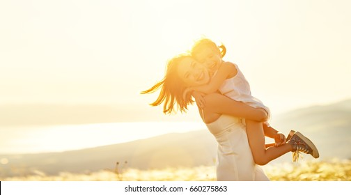 Happy family in the summer outdoors. mother and child. daughter, hugs and laughing