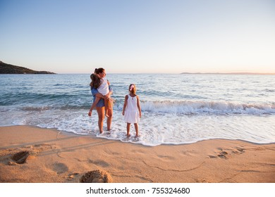 Happy Family summer travel vacation, mother with daughters enjoying sunset on sand beach.