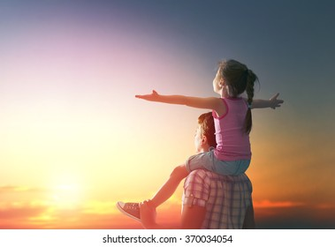 happy family at sunset. father and daughter having fun and playing in nature. the child sits on the shoulders of his father.
