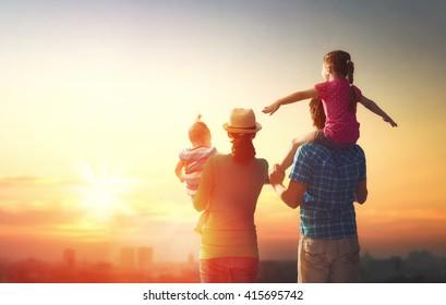 일몰 때 행복한 가족아버지, 어머니, 두 딸.그 아이는 아버지의 어깨에 앉아 있다.