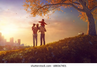 Happy family at sunset. Father, mother and two children daughters having fun and playing on autumn nature. The child is sitting on the shoulders of his father.