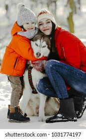 Happy family at sunset. Mother and sun are having fun and playing on snowy winter walk in nature with dog husky. Frost winter season. Portrait of a cheerful family with dog.