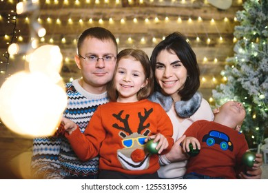 happy family in sweaters in christmas house