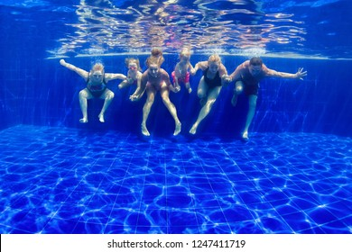 Happy family in swimming pool. Smiling mother, children and grandparents swim, dive in pool with fun - jump deep down underwater. Healthy lifestyle, people water sport activity on holidays with kids