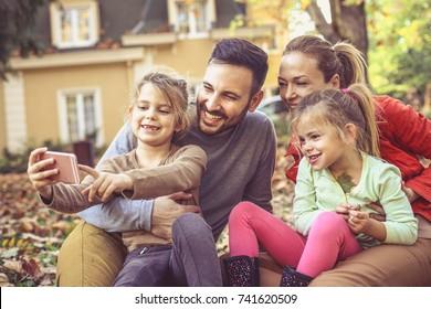 Happy family take a self portrait sitting at backyard.