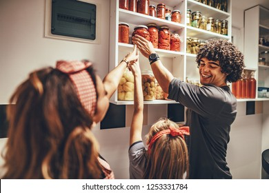 A happy family takes jars with pickled vegetables from the pantry shelf.