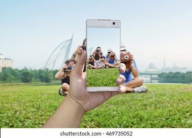 Happy family taking a photo of themselves at picnic