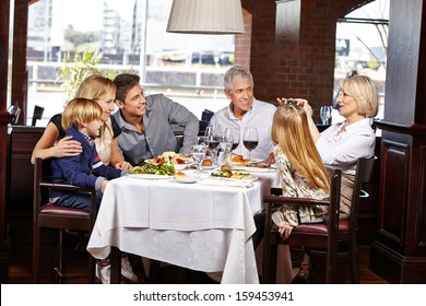 Happy family taking pictures with camera in a restaurant