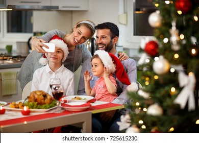 Happy family taking selfie at decorated Christmas table with tasty food