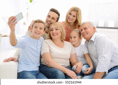 Happy family taking selfie in living room