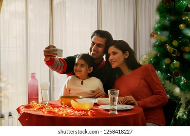Happy family taking selfie with mobile phone while having meal during Christmas