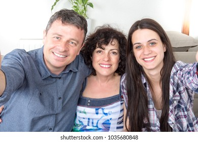 Happy family taking a selfie on the couch with smartphone in living room holidays and technology people concept