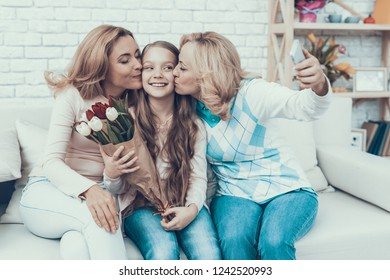 Happy Family Taking Selfie on Daughter's Birthday. Happy Family. Mother with Daughter. Smiling Women. Smiling Grandmother. Celebration Concept. Using Smartphone. Taking Photo. Bouquet in Hands.
