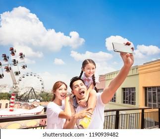 szczęśliwa rodzina biorąc selfie w park