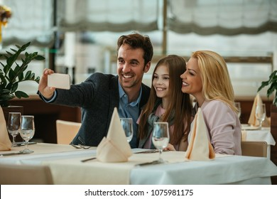 Happy family taking a selfie in a restaurant