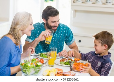 Happy family talking to each other while having meal in kitchen at home
