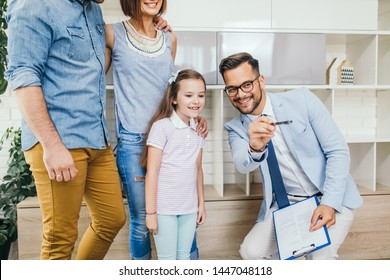 Happy family talking with real estate agent about buying a new home.