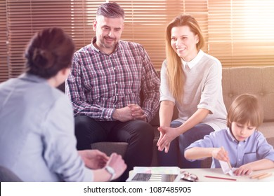 Happy family talking with their son's teacher in the office