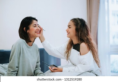 Happy Family teenage daughter is makeup to the mother in the bedroom in the morning before working.