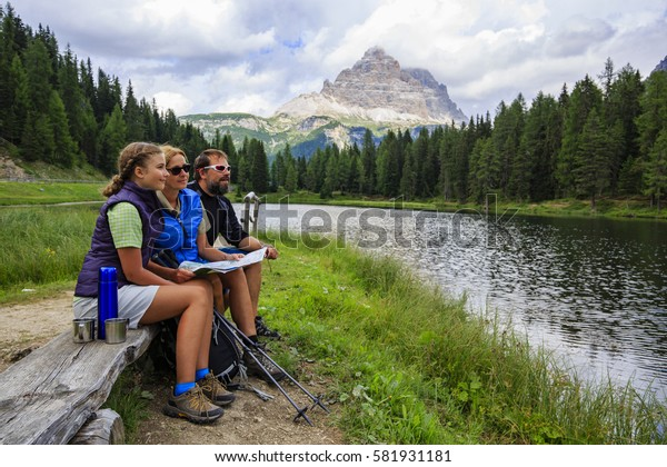 Happy family with teenager taking rest tee brake during trekking day on Dolomites mountain in summer time in Italy. Concept of travel, friendly family.