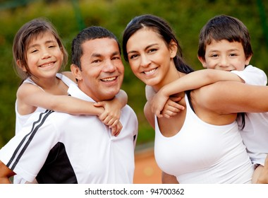 Happy family of tennis players at the court