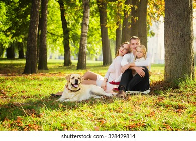 Happy family with their dog in the park on a sunny day