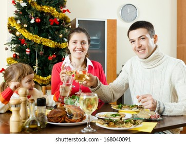 Happy family of three celebrating Christmas  over celebratory table at home interior
