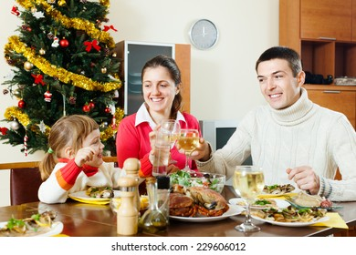Happy family of three celebrating Christmas over  table