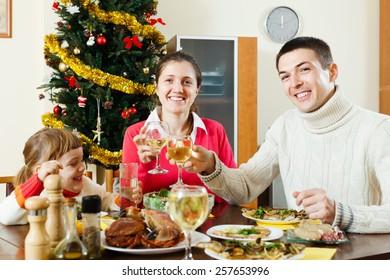 Happy family of three celebrating Christmas over celebratory table