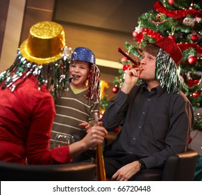 Happy family of three celebrating in new year eve hat at home.?