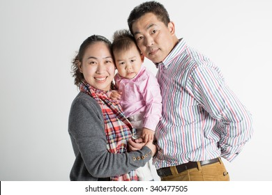 happy family of three family of china, in a studio shoot their photos