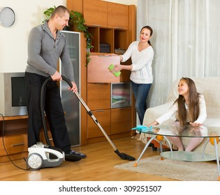 Happy family of three cleaning in the living room all together. Selective focus