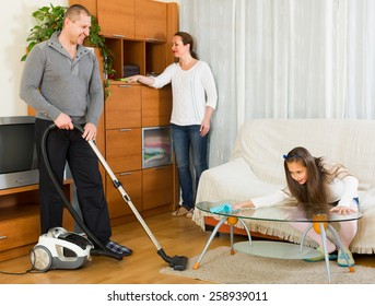 Happy family of three cleaning up a room all together. Focus on man