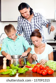 Happy family of three cooking veggie lunch together in home kitchen