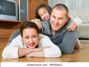 Happy family of three in domestic interior
