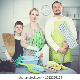 Happy family of three dressed for cleaning, standing in home interior