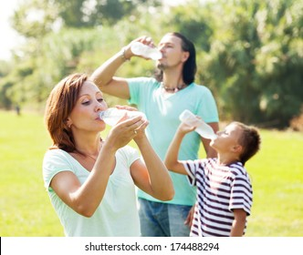 Happy family of three drinking from plastic bottles in summer park