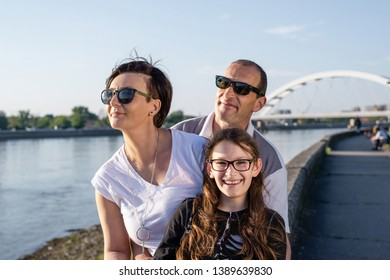 Happy family of three enjoying view over the river Danube at sunset. All wearing glasses, sitting on the river bank behind each other. Cute ten year old girl smiles at camera