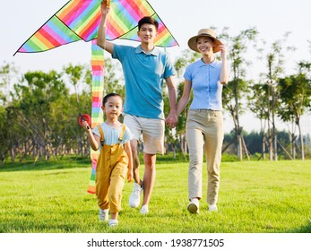 Happy family of three flying kites in the park smiling
