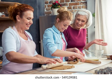 Happy family of three generations preparing gingerbread cookies rolling the dough