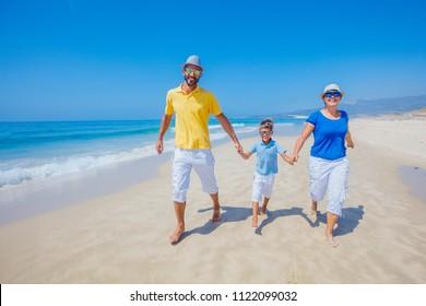 Happy family of three having fun running on a sandy beach