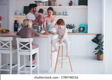 happy family with three kids having breakfast at the kitchen in the morning