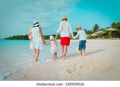 happy family with three kids walk on beach