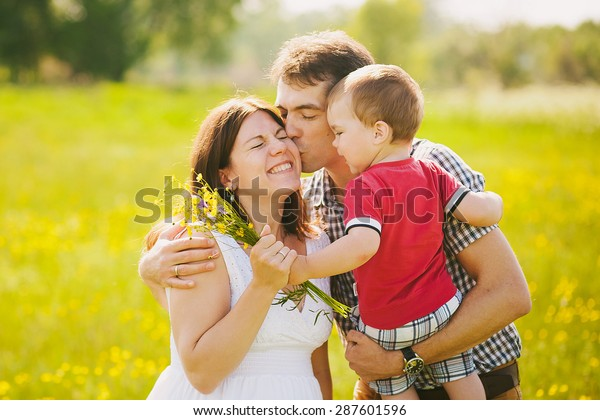 Happy family of three kissing outside. Mother in expectation of baby. Smiling faces of woman, man and child. Baby playing outdoors with parents. Togetherness. Man and woman hugging in sunset time.