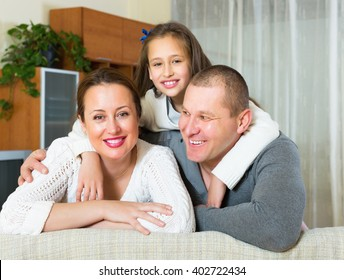 Happy family of three in livingroom at home