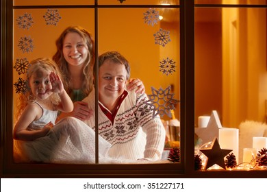 Happy family of three looking through the window at night. Christmas greeting card or cover.