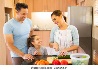 happy family of three making salad in kitchen