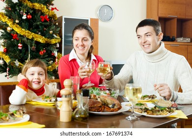 Happy family of three over celebratory table at home