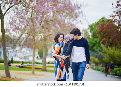 Happy family of three in Paris on a spring day with purple jacarandas in full bloom. Mother, father and little son enjoying their family time and vacation to France