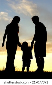 A happy family of three people, mother, father, and toddler, are holding hands and walking toward the sunset, silhouetted against the sky.
